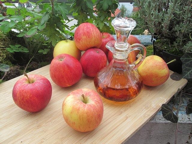 Спелые яблоки на столе и графин с уксусом