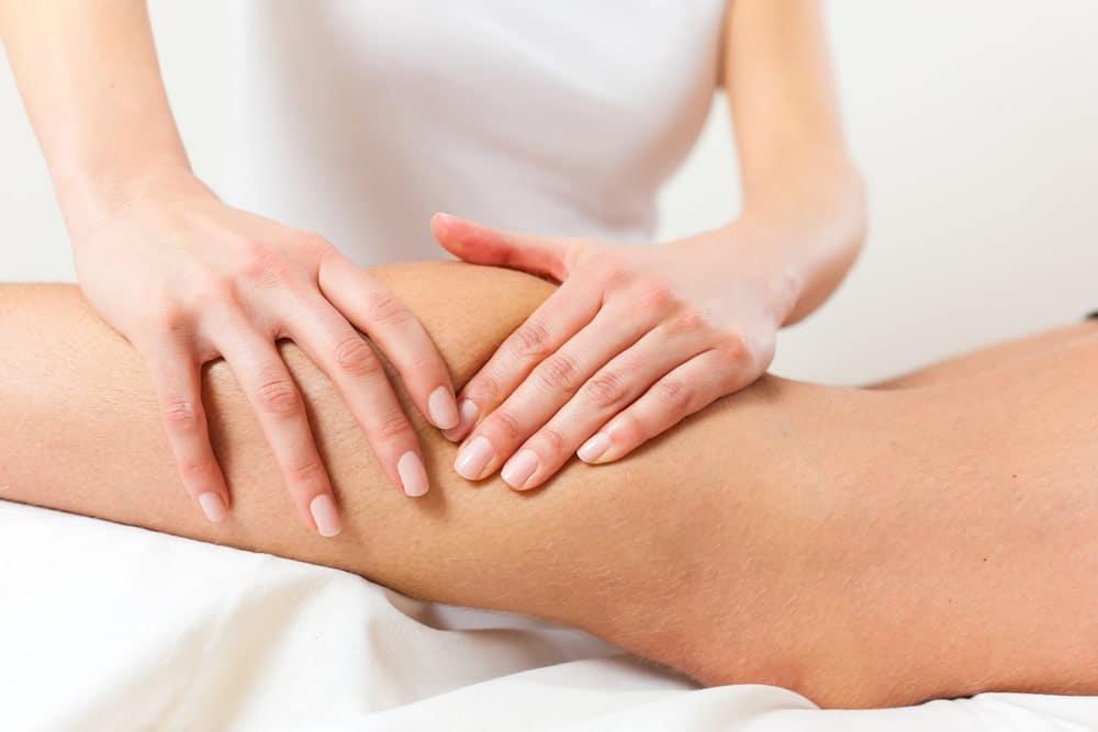 Массажист делает лимфодренажный массаж на ноге пациента